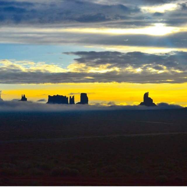 Sunrise over the buttes as the fog lifts.  Monument Valley
